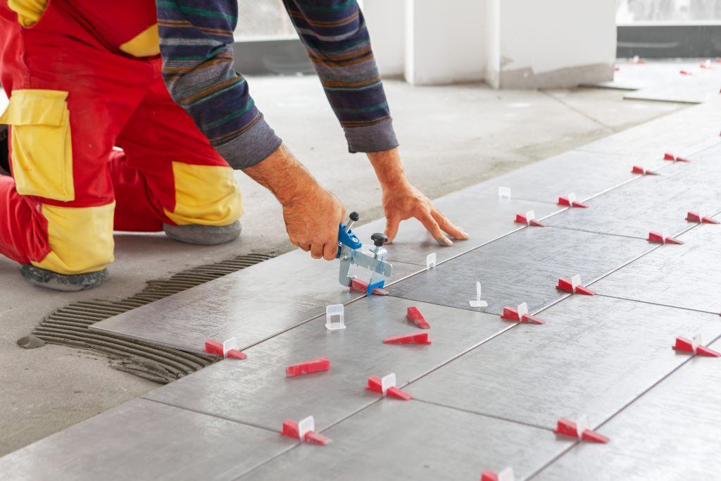 Ceramic Tiles. Tiler placing ceramic wall tile in position over adhesive with lash tile leveling system - Image